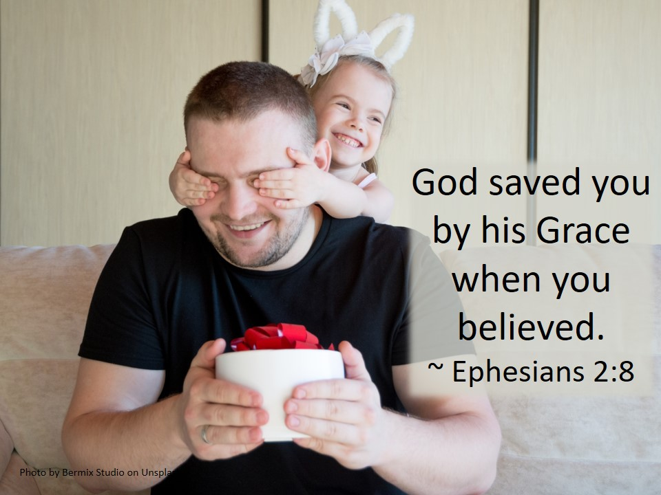 """Girl covering her dad's eyes while he is holding a present. This illustrates the grace aspect of the text: God saved you by his Grace when you believed."""""""